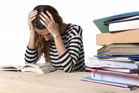 stock photo of investigation  - young stressed student girl studying pile of books on library desk preparing MBA test or exam in stress feeling tired and overwhelmed in youth education concept - JPG