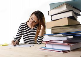 pic of piles  - young student girl concentrated studying with textbook at college library desk with piles of books preparing MBA test or exam in academic wisdom and education concept - JPG