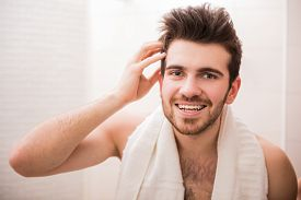 pic of male pattern baldness  - Handsome young man is looking at the mirror and smiling - JPG