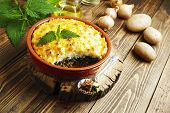 foto of nettle  - Potato casserole with meat and nettle on the table - JPG