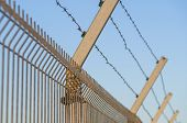 picture of barbed wire fence  - Security post with barbed wire fence closeup - JPG