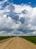 picture of dirt road  - Barren empty dirt road points to the horizon as dark rain clouds gather overhead - JPG