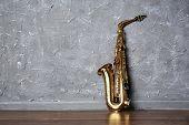 stock photo of saxophones  - Golden saxophone on gray wall background - JPG
