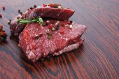 stock photo of peppercorns  - fresh raw beef fillet mignon on old retro style wood as background with rosemary peppercorn and salt - JPG