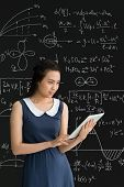 stock photo of formulas  - Smiling Asian college student using digital tablet against blackboard with formulas - JPG
