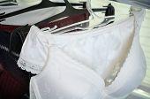 stock photo of white satin lingerie  - white black and vinous lace lingerie hanging on the hanger close up - JPG