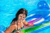 foto of mattress  - Happy woman  swimming on inflatable beach mattress - JPG