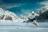 foto of ice hockey goal  - Ice hockey player in action outdoor around mountains - JPG