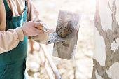 foto of mason  - Mason putting decorative natural stones on a wall - JPG