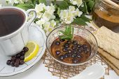 stock photo of chokeberry  - Chokeberry tea in a porcelain cup on a flower decorated table - JPG