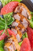 image of roast duck  - Roast duck breast with lettuce and grapefruit on a plate - JPG