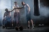 foto of gym workout  - Rest three guys who have completed a complex crossfit workout in the gym - JPG