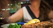 pic of lobster tail  - Steak and Lobster platter on white dish sitting in front of a blurred woman moving her folk towards green beans while sitting in a restaurant booth - JPG