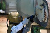 foto of sandblasting  - Worker is removing paint by air pressure sand blasting - JPG