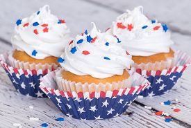 stock photo of sprinkling  - Cupcakes with patriotic 4th of July sprinkles on vintage background shallow depth of field - JPG