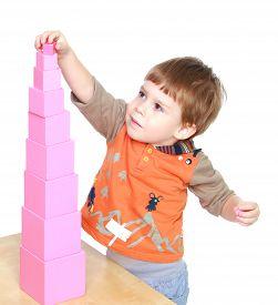 stock photo of human pyramid  - Little boy learn to put pink pyramid in Montessori kindergarten - JPG
