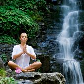 Beautiful young woman meditating in lotus position while doing yoga in a wonderful forest near waterfall