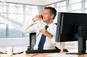 Succesvolle zakenman zit aan zijn bureau tijdens het gesprek op mobiele