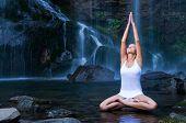 Постер, плакат: Красивая молодая женщина делать позу лотоса йоги в бассейн с водой возле водопада