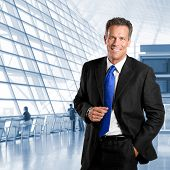 Empresário de sucesso maduro, sorrindo e olhando para a câmera em um edifício de escritório moderno