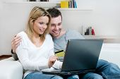 foto of internet shop  - Young couple doing shopping in internet with credit card at home - JPG