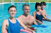 Happy active people exercising with aqua tube in water swimming pool