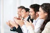 Happy lächelnd Business Team Händeklatschen während einer Sitzung im Büro