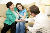 Therapist congratulates mother and daughter on successfully completing therapy.