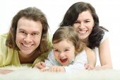 Happy young family - mother, father and playful little daughter - are lying on a white fluffy fur and laughing poster