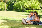 stock photo of keepsake  - Family looking at their photo album in the park - JPG