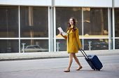 travel, trip, tourism, people and vacation concept - happy young woman with carry-on travel bag and  poster