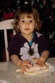 Beautiful little girl making cookies
