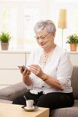 Senior woman sitting on sofa, using palmtop, smiling.?