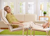 Woman relaxing at home, sitting in armchair with crossed feet up on footboard, smiling at camera.?