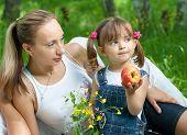 Liegen Mutter und Tochter In Jeans mit Apple im freien