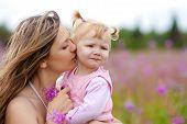 Mutter küssen Tochter auf Wiese im freien