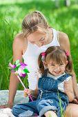 lächelnd Mutter und Tochter in Jeans mit bunten Spielzeug outdoor