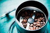 Electrical coffee-mill machine with roasted coffee beans on the green tabletop without top cover
