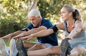 Mature couple stretching at park and listening to music. Athletic senior couple exercising together  poster