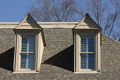 Two Dormers On Gray Shingled Roof Under Winters Sky