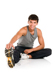 foto of fitness man body  - Happy smiling young fitness man sitting and making stretching exercises after gym isolated on white background - JPG