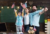 Kid With Parents In Classroom With Usa Flags, Chalkboard On Background. Parents Teaching Son America poster