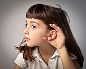Little girl lending an ear to something