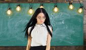 Lady Strict Teacher On Calm Face Stands In Front Of Chalkboard. Woman With Long Hair In White Blouse poster