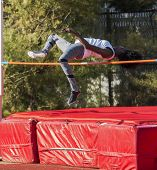 Female High School Track And Field Athlete Is Over The Bar While Competing In The High Jump. poster