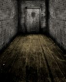 Grunge style image of passageway leading to an old prison door