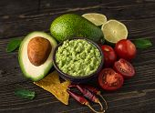 Guacamole In Blue Bowl With Tortilla Chips And Lemon On Natural Wooden Desk. poster