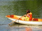 A Girl In A Life Jacket Floats On A Rowing Boat On A Summer Lake. Young Woman Rowing With Oars, Safe poster