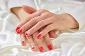 Female Well-groomed Hands On Silk. Womans Hands With Beautiful Romantic Manicure On White Silk Mater poster