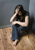 pic of depressed teen  - Teenage girl sitting on floor with scattered pills contemplating suicide - JPG